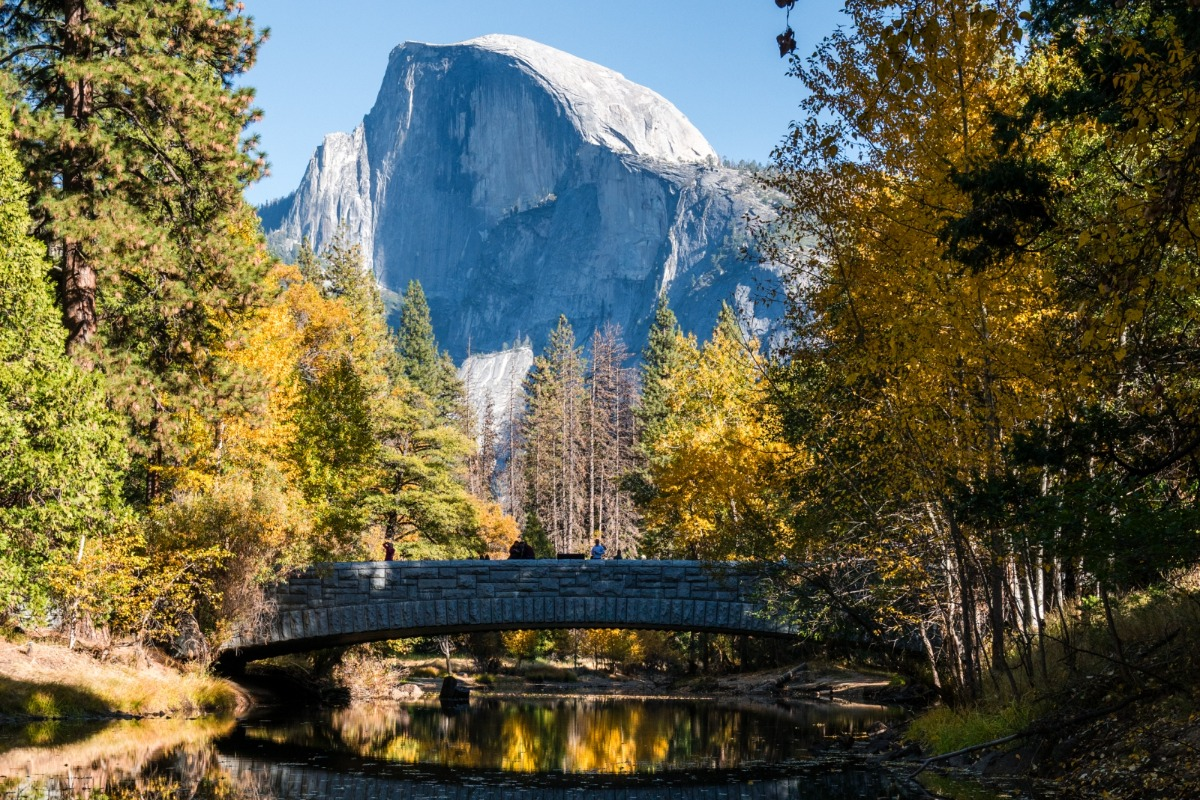 Yosemite's Half Dome surrounded in fall colors and reflected in the Merced River with Sentinel Bridge in the foreground