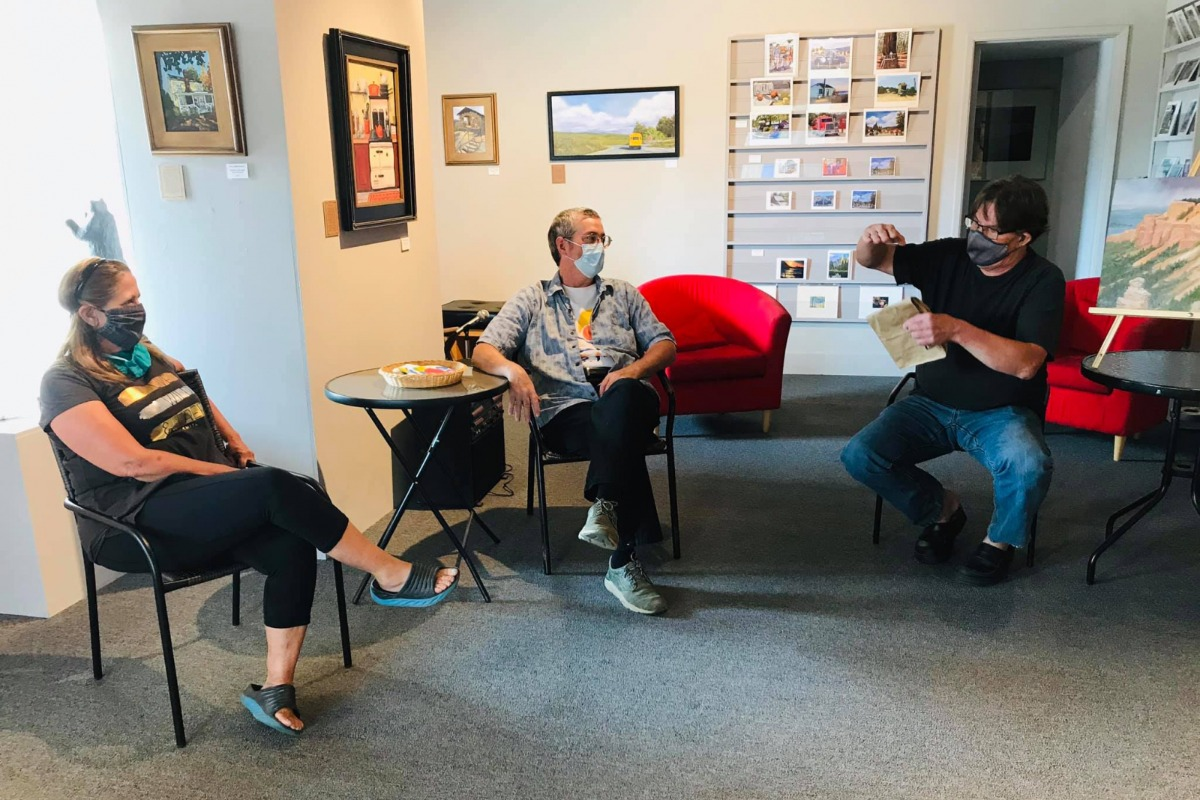 Artists Faith Rumm, Jon Bock, and Jon Kifer swapping stories at the Art Center Gallery